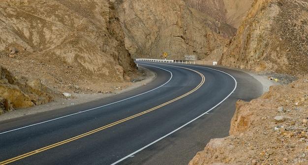 Strada sinuosa vuota nel mezzo di scogliere e montagne