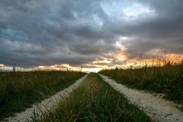 Strada sterrata tra campi scuri al tramonto con drammatico cloudscape.