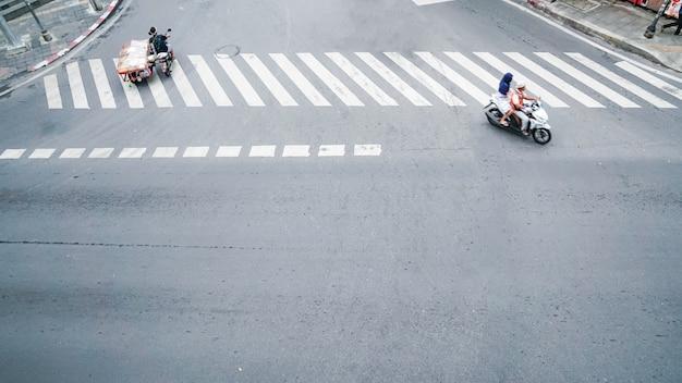 Strada sulla vista superiore con il segno di attraversamento pedonale sulla strada e auto e moto