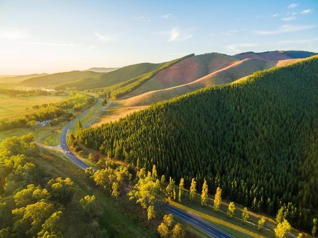 Strada tortuosa che attraversa la bellissima campagna australiana al tramonto
