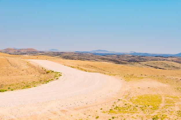 Strada tortuosa di ghiaia che attraversa il colorato deserto del namib, nel maestoso namib naukluft national park, la migliore destinazione di viaggio in namibia, africa.