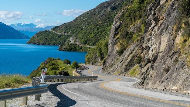 Strada tortuosa lungo la scogliera e il lago della montagna