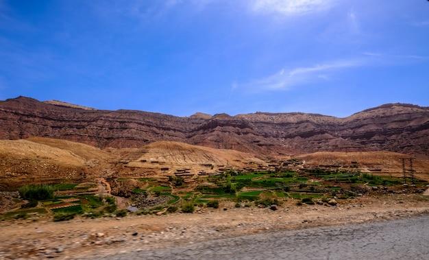 Strada vicino ai campi erbosi con montagne sabbiose in lontananza e un cielo blu