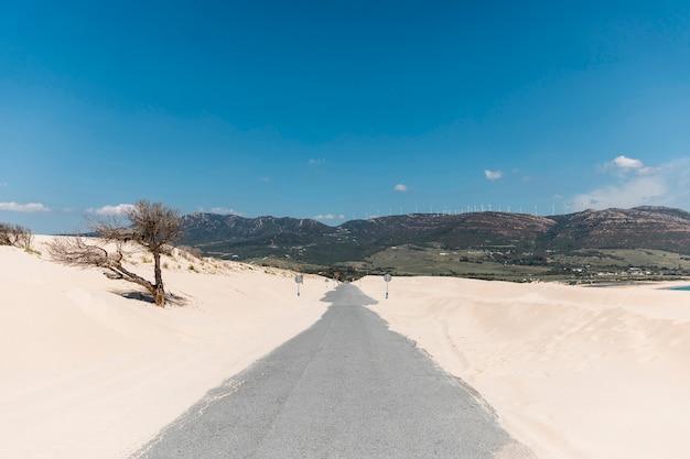 Strada vuota in sabbie contro montagne