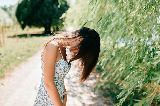 Strana giovane modella caucasica gettando i suoi lunghi capelli in aria. dancing teenager sveglio all'aperto nel parco di estate. ritratto insolito di stile di vita strano della ragazza adorabile che scuote testa alla natura. strana persona eccentrica.