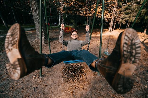 Strano bizzarro concetto di persone eccentriche. uomo adulto in stivali alla moda vintage cavalcando altalena nel parco cittadino sul parco giochi per bambini. le gambe si spalancarono