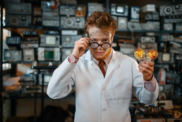Strano ingegnere tiene lampada elettrica in laboratorio.
