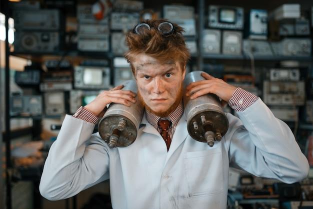 Strano scienziato tiene dispositivi di radiazione nelle sue mani, test pericoloso in laboratorio.