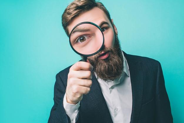 Strano uomo guarda dritto attraverso la lente d'ingrandimento
