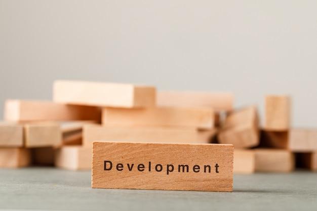 Strategia aziendale e concetto di successo con i blocchi di legno sulla vista laterale della parete grigia e bianca.