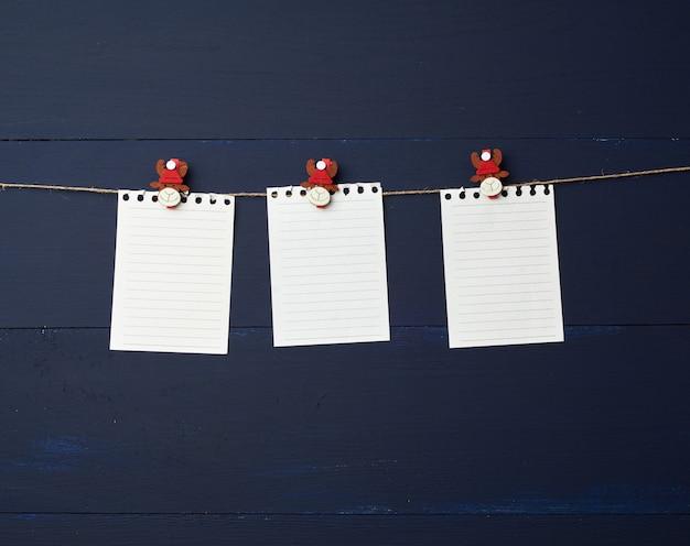 Strati bianchi vuoti della carta del taccuino che appendono sulle mollette da bucato decorative di festa
