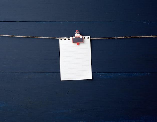 Strato di carta bianco vuoto del taccuino che appende sulla molletta da bucato decorativa di festa