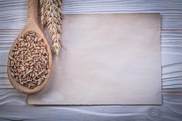 Strato di carta d'annata del cucchiaio di legno del mais di legno dorato delle orecchie della segale sul concetto di legno dell'alimento e della bevanda del bordo