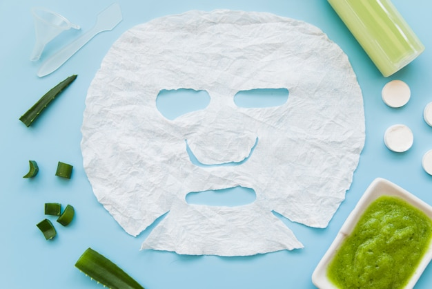 Strato di carta del viso bianco con aloevera su sfondo blu