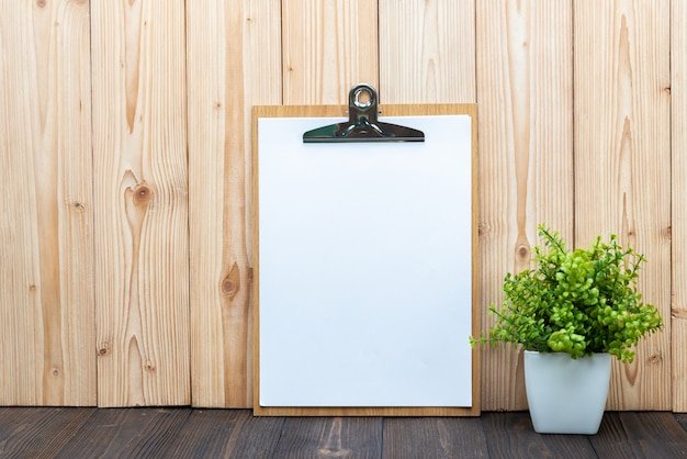 Strato in bianco del blocco per appunti della lavagna per appunti con il piccolo albero della decorazione in vaso bianco su fondo di legno