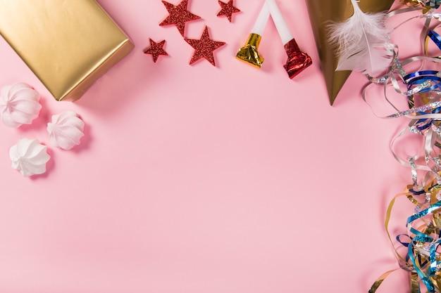 Streamers; adesivi stelle; pacco regalo; cappello da festa; piuma; zeffiri e soffiatori di partito sullo sfondo rosa