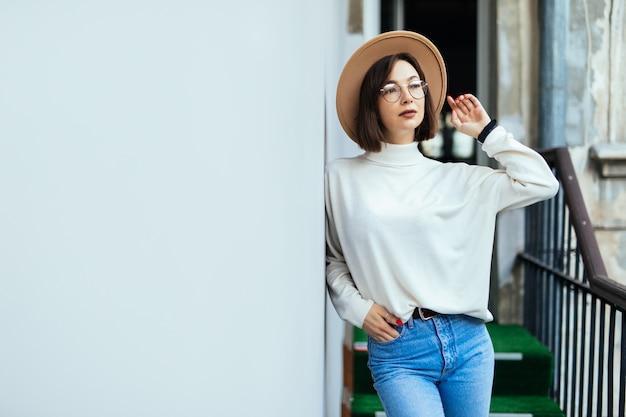 Street fashion donna interessata che indossa cappello, blue jeans, cappello largo e occhiali trasparenti sul balcone