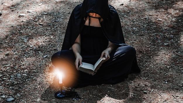 Strega con il tomo e la candela accesa che si siede sulla terra del boschetto