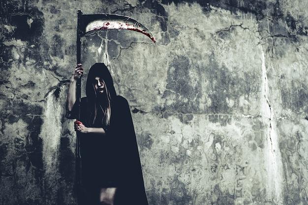 Strega del demone con la reaper che si leva in piedi davanti alla priorità bassa della parete del grunge.