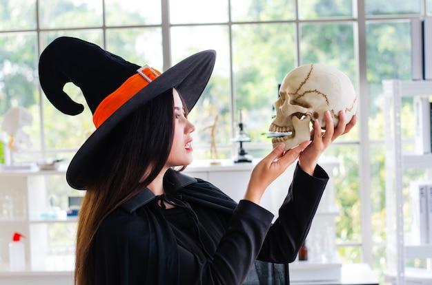 Strega di halloween, bella giovane donna in cappello e costume delle streghe
