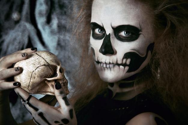 Strega di scheletro della ragazza che posa nelle ragnatele, halloween