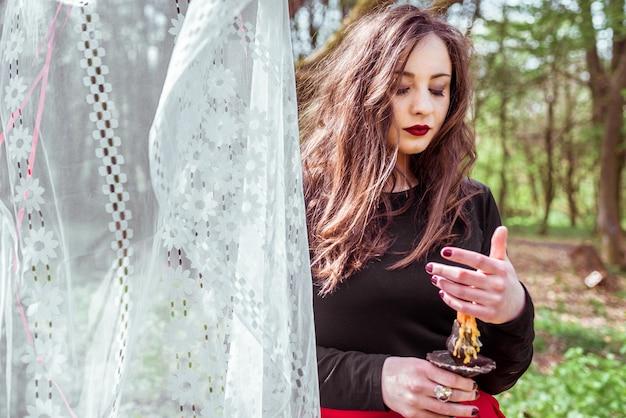 Strega nel bosco con una candela