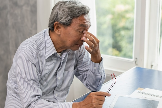 Stress degli anziani asiatici stanchi e con il naso soffre di affaticamento da dolore al seno.
