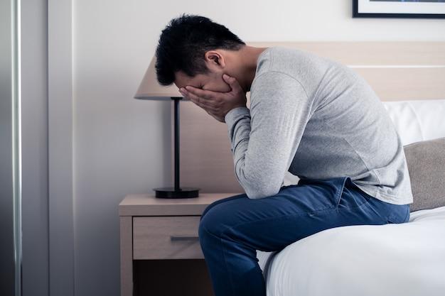 Stress giovane asiatico seduto da solo sul letto e piangendo con lacrime e coprirsi il viso con entrambe le mani.