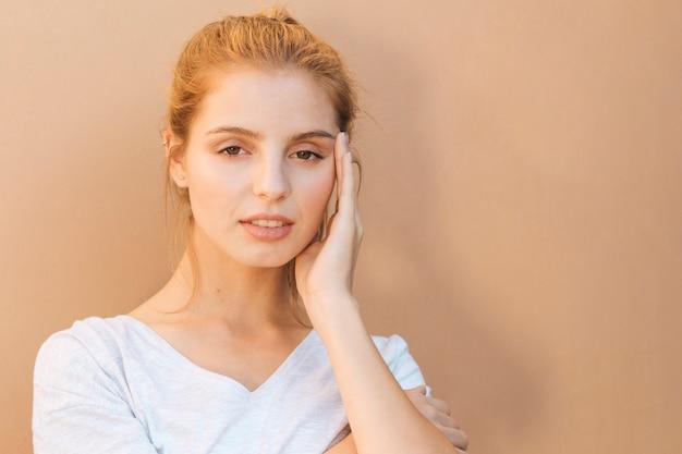 Stressante giovane donna con la sua mano sul viso su sfondo beige