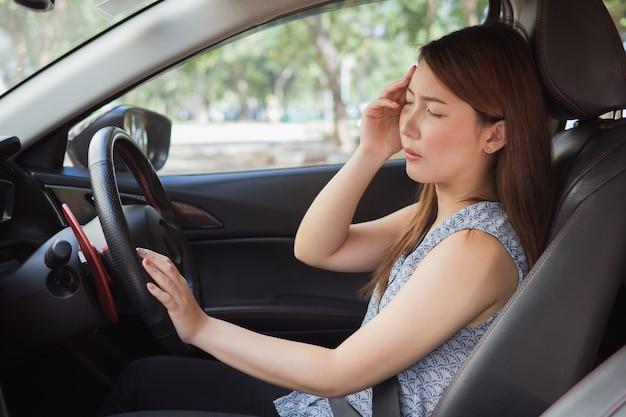 Stressato di autista donna asiatica seduto all'interno della sua auto