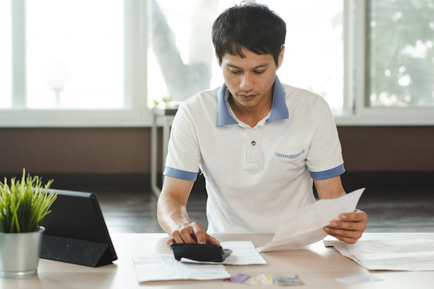 Stressato uomo calcolo debito della carta di credito.