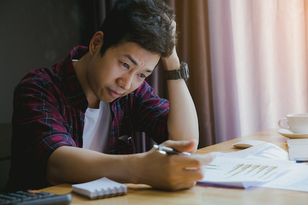 Stressato uomo. un giovane uomo siede alla sua scrivania e tiene le mani in testa a causa dello stress e del rapporto di sintesi.