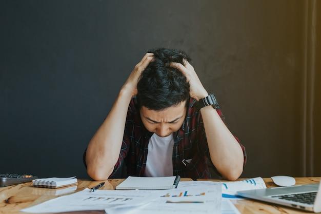 Stressato uomo. un giovane uomo siede alla sua scrivania e tiene le mani
