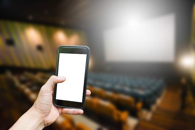 Stretta della mano sul cellulare con sfondo del cinema