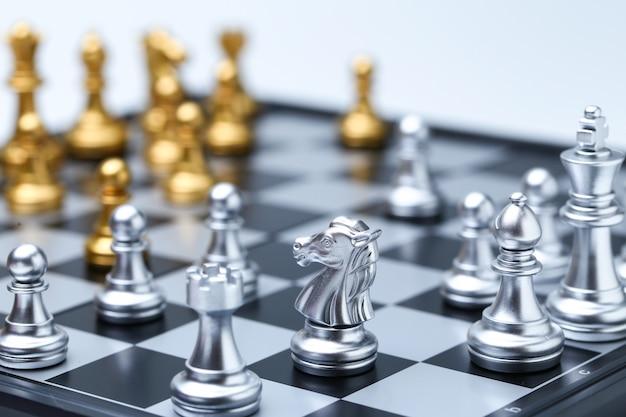 Stretta di cavaliere sulla scacchiera e pezzi degli scacchi