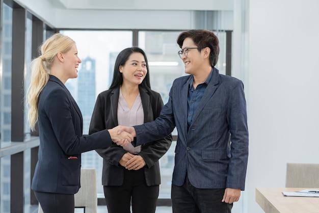 Stretta di mano asiatica delle coppie della famiglia con l'agente immobiliare della proprietà dopo l'acquisto del contratto di mutuo per la casa fatto accordo