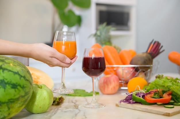 Stretta di mano che tiene un bicchiere di succo sano, mentre le verdure e gli spremiagrumi sul tavolo in cucina, il concetto di salute