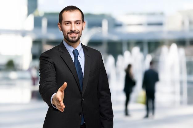 Stretta di mano d'offerta dell'uomo d'affari bello in un ambiente urbano