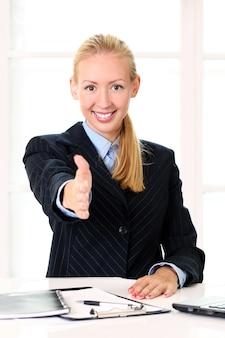 Stretta di mano d'offerta della giovane donna di affari