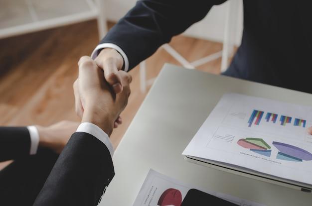 Stretta di mano del partner della gente dell'investitore di affari del gruppo dopo aver finito la riunione d'affari con le statistiche finanziarie riferiscono sullo scrittorio in ufficio