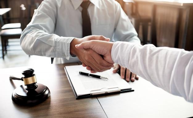Stretta di mano dell'avvocato con il cliente. associazione di affari che incontra concetto riuscito.