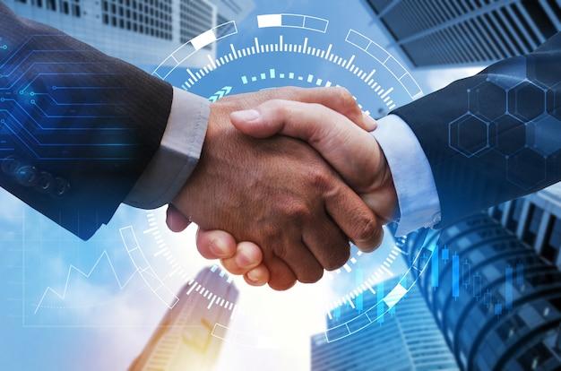 Stretta di mano dell'uomo d'affari con connessione di rete globale, grafico del mercato azionario diagramma grafico e lo sfondo della città, tecnologia digitale, comunicazione internet, lavoro di squadra, concetto di partenariato