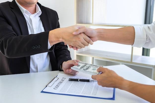 Stretta di mano dell'uomo d'affari con i soldi delle banconote del dollaro nelle mani dal denaro per dare il successo l'affare