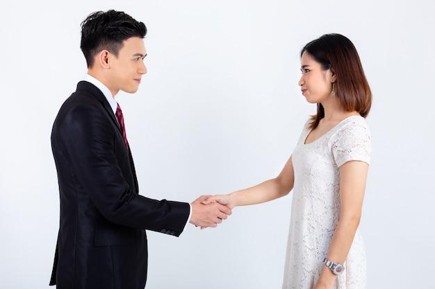 Stretta di mano dell'uomo d'affari con la giovane donna di segretaria su bianco