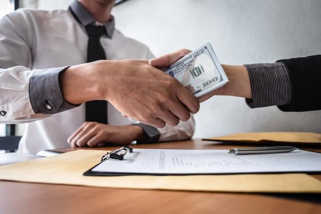 Stretta di mano dell'uomo d'affari con soldi delle banconote del dollaro in mani da mentre danno il contratto di successo