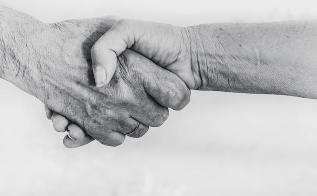 Stretta di mano dell'uomo maggiore e della donna su bianco