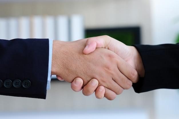 Stretta di mano della donna e dell'uomo d'affari all'ufficio, cooperazione di affari, successo negli affari