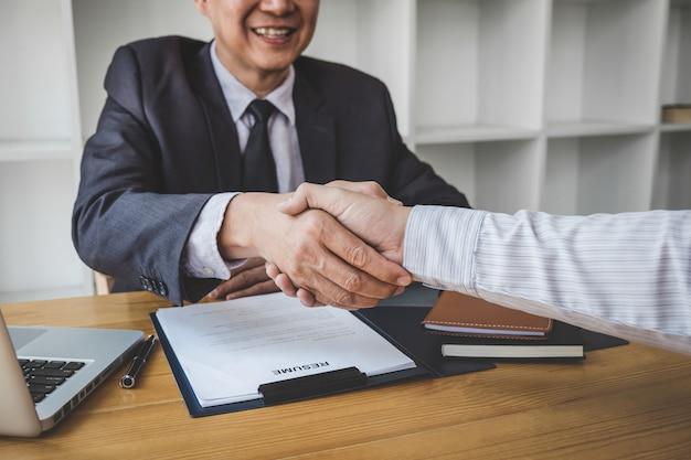 Stretta di mano durante il colloquio di lavoro, candidato che stringe la mano all'intervistatore o al datore di lavoro