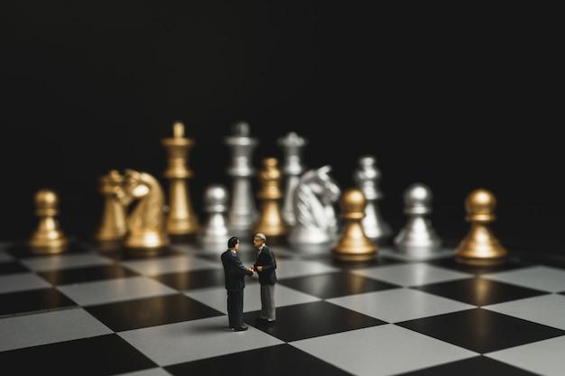 Stretta di mano in miniatura di uomo d'affari con sfondo di scacchi oro e argento.