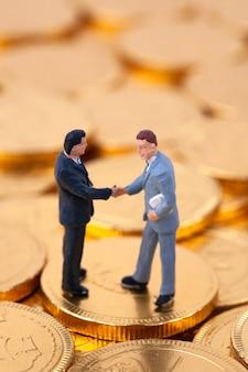 Stretta di mano in miniatura uomo d'affari su monete d'oro